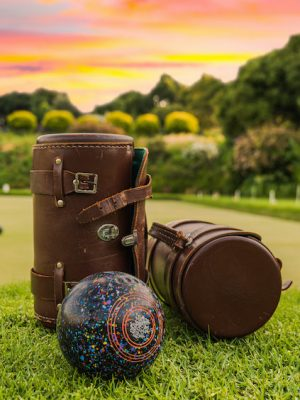 Lawn bowls leather bags and balls on the field side while players are playing at sunset